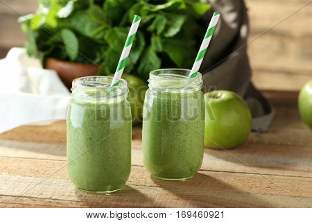 Tasty milk shake cocktails with spinach and apples on wooden table