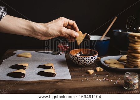 Man Dipping Heart Shaped Biscuit in Melted Chocolate on Rustic Wooden Table