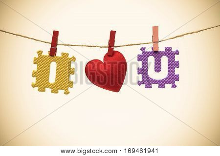 Love for Valentine's day - Red heart with I and u jigsaw hung on a rope