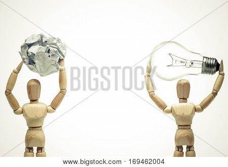 Two wood figure mannequins carrying an incandescent light bulb and a crumpled paper ball / Being smart vs. stupid