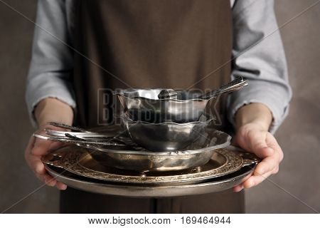 Closeup of woman holding tray with silver dishware