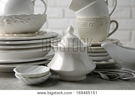 Porcelain dishware on table and white brick wall background