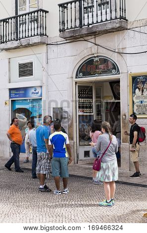 LISBON, PORTUGAL - September 26, 2016: Locals and tourists alike enjoying a Sour Cherry Liqour at A Ginjinha the famous liqour shop in Lisbon Portugal