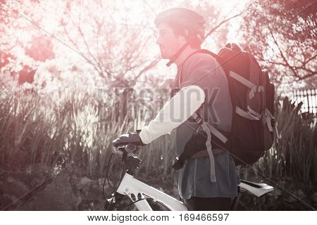 Side view of male mountain biker with bicycle in forest on sunny day