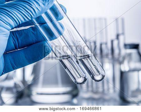 Laboratory beakers in analyst's hand in plastic glove.