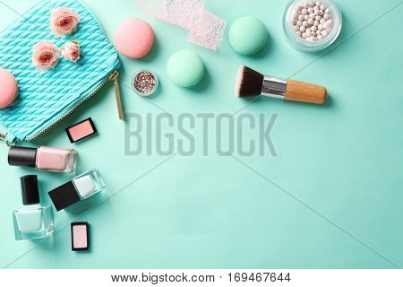 Makeup products with cosmetic bag and macaroons on color background