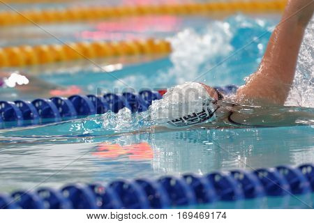 ST. PETERSBURG, RUSSIA - DECEMBER 16, 2016: Female athlete competes in 50 m backstroke swimming competition during X Salnikov Cup. Athletes from 6 countries participated in the competitions