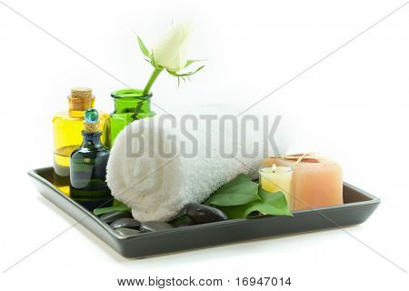 relaxation spa set with candles, essential oils, towel, pebbles and fresh flowers, suited for spa and healthy lifestyle usage.