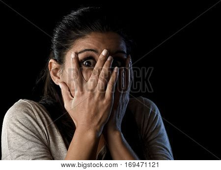 close up portrait young attractive Latin woman desperate and scared isolated on black background looking terrorized and horrified covering her eyes in primal fear emotion face expression