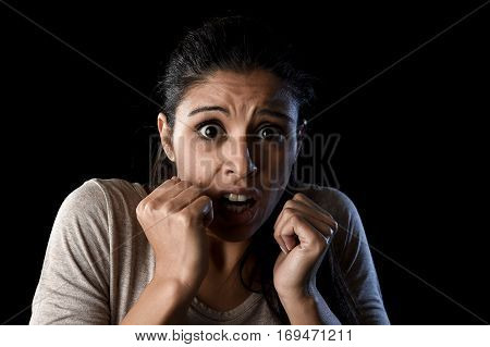 close up portrait young attractive Latin woman desperate and scared isolated on black background looking terrorized and horrified in primal fear emotion face expression