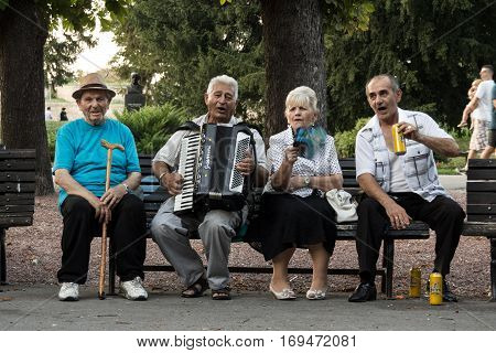 BELGRADE SERBIA - AUGUST 30 2015: Serbian old people celebrating playing accordeon and drinking local beer