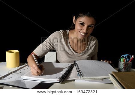 young busy beautiful Spanish girl smiling happy and confident studying at home late night looking preparing exam concentrated and quiet in education concept