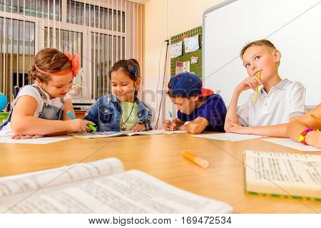 Group of students studying with interest at a lesson at school. Educational concept.