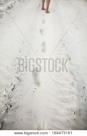 Person leaving footprints in sand at the beach