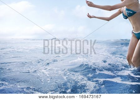 Woman tossing water into air at the beach