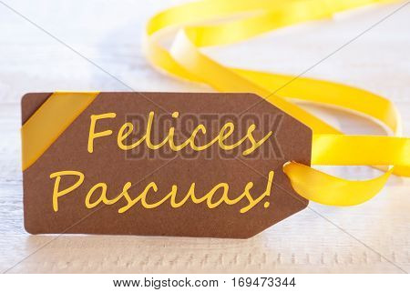 Label With Spanish Text Felices Pascuas Means Happy Easter. White Wooden Background. Card For Seasons Greetings Or Easter Greetings