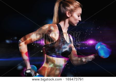 Muscular woman is training with perfect fit in shiny background