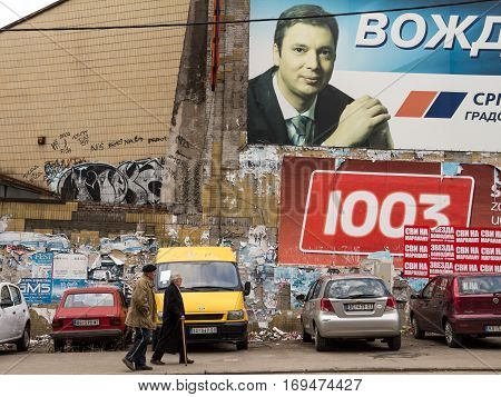 BELGRADE SERBIA - MARCH 8 2015: Old people walking in front of a propaganda poster for the Prime Minister Aleksandar Vucic