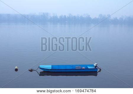 Rowing boat on the Danube on a foggy dusk in winter in Zemun Belgrade Serbia