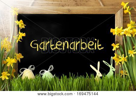 Blackboard With German Text Gartenarbeit Means Gardening. Sunny Spring Flowers Nacissus Or Daffodil With Grass, Easter Egg And Bunny. Rustic Aged Wooden Background.