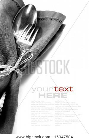 Spoon and fork in textile napkin over white with sample text