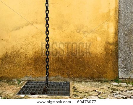 Rustic metal chain with links going into a metal grate with a yellow rusty looking background wall and a stone wall with space for text.