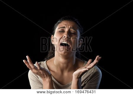 young attractive sad and desperate Latin woman crying frustrated suffering pain and problems grieving in stress and sorrow in facial expression of sadness emotion isolated on black background