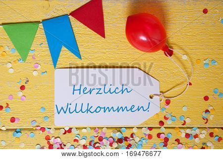 White Label With German Text Herzlich Willkommen Means Welcome. Party Decoration Like Streamer, Confetti And Balloon. Flat Lay Or Top View. Yellow Wooden Background