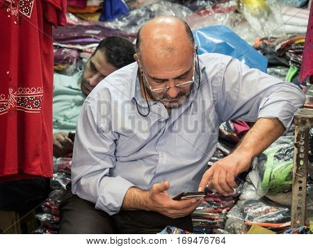 TEHRAN IRAN - AUGUST 14 2016: Iranian merchants using their smartphones in Tehran bazaar. Iran is among the first five countries which have had a growth rate of over 20 percent and the highest level of development in telecommunication.