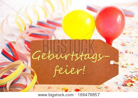 One Label With German Text Geburtstagsfeier Means Birthday Party. Party Decoration Like Streamer, Confetti And Balloons. Wooden Background With Vintage, Retro Or Rustic Syle