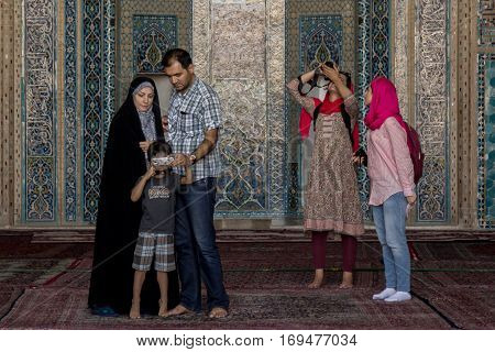 YAZD, IRAN - AUGUST 18, 2016: Contrast between a traditional iranian family with a woman wearing hijab and foreign tourists both groups taking pictures in Jame Mosque, one of Yazd landmarks