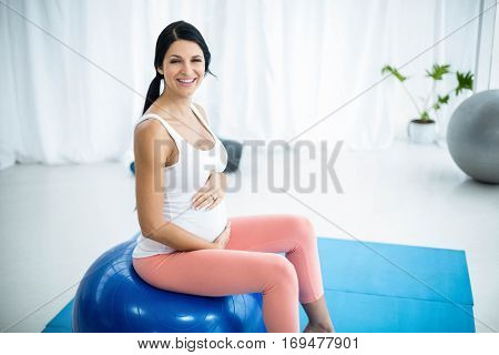 Portrait of pregnant woman exercising while sitting on exercise ball at home