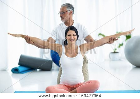 Portrait of doctor examining and giving physiotherapy to pregnant woman