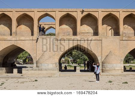 ISFAHAN IRAN - AUGUST 20 2016: People taking selfies on and next to Si o Seh Pol bridge in Iran