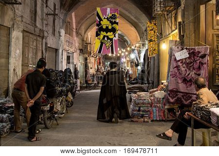 ISFAHAN IRAN - AUGUST 20 2016: Imam passing under a Batman logo in Isfahan bazaar