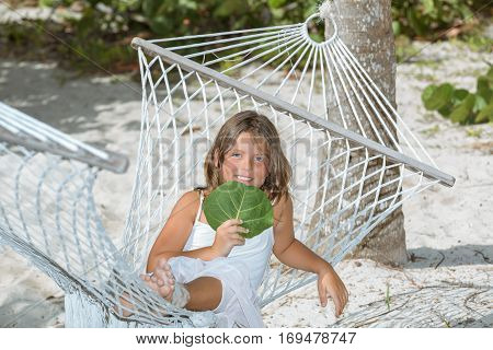 happy, joyful smile little girl sitting on hammock and enjoying her leisure, siesta time in tropical cozy garden