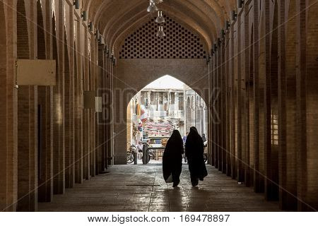 ISFAHAN IRAN - AUGUST 20 2016: Women wearing the islamic veil walking in a street of the covered bazaar of Isfahan