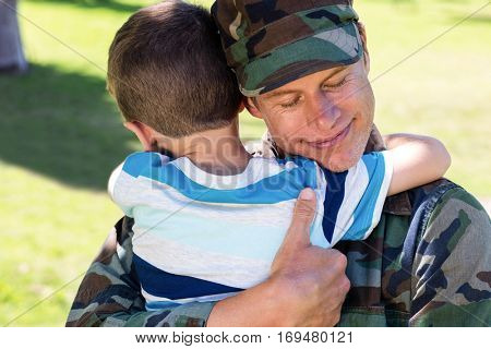 Happy soldier reunited with his son in the park on a sunny day