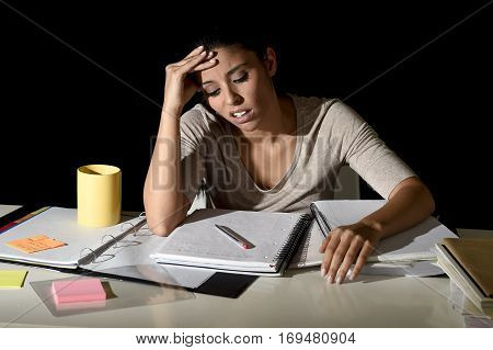 young beautiful Spanish girl studying tired and bored at home late night looking sad and stressed preparing exam in overwhelmed and frustrated face expression in education stress concept