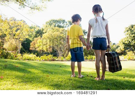Rear view of children holding their hands looking forward while holding a luggage in a park
