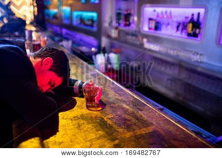 Drunken man sleeping on bar counter at restaurant