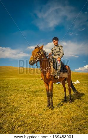Boy In Sweater On Horse In Kyrgyzstan