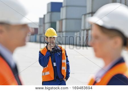 Worker using walkie-talkie while colleagues discussing in foreground at shipping yard