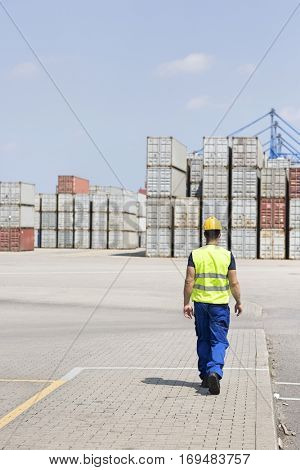 Full-length rear view of male worker walking in shipping yard