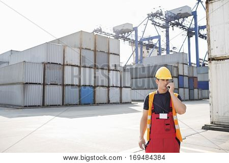 Mid adult man using walkie-talkie in shipping yard