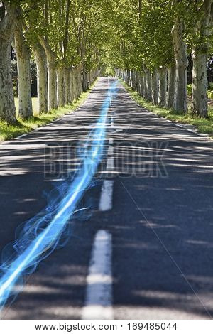 Blue streak of light on country road along trees