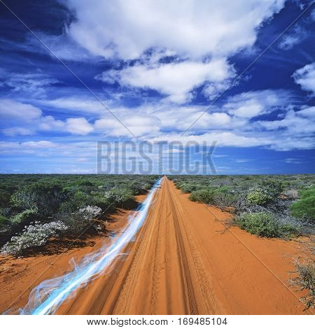 Blue streak of light on dirt road against cloudy sky