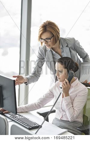 Businesswoman using landline phone while manager pointing towards computer in office
