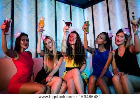 Portrait of happy friends sitting together and showing mocktails in bar