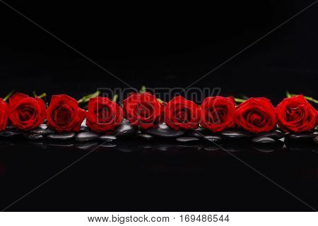 Still life with Row of red rose and therapy stones